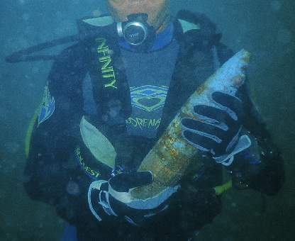 High Explosive large caliber shell being played with by a recreational scuba diver. Prat.